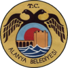A dark-yellow circular seal with a smaller circle inside it that portrays a fortified tower and wall behind blue waves. The smaller circle is enclosed by a black two-headed bird with the text T.C. above and Alanya Belediyesi below.
