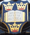 "A shield displaying a coat of arms; on a dark blue background, an open book displays the words ""Dominus Illuminatio Mea""; two gold crowns above, one below"