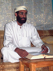 A man in white clothing with a beard and glasses sits cross-legged before a table with an open book.