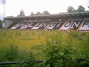 A grandstand whose coloured seats spell out the word Darlington. A floodlight pylon stands at one end. The stand faces a grassed area overgrown with weeds.