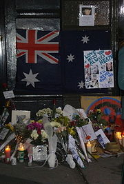 "Dark doorway and doorstep with section of footpath. On the lower part of the dark door is a partly obscured Australian flag with dark blue background; red and white crosses on top left, large white star underneath and three white stars at the right with others obscured. Obsuring the right side of the flag is a white sheet with light blue writing, ""Love + Miss You Always Heath"" with two red hearts nearby, other writing includes ""I'll never quit you"" in darker blue, more writing is indistinct. This sheet also has six photos of a man. Above the flag, on the door is a smaller sheet with a photo of a man and indistinct writing below. On the doorstep and section of footpath are some 14 groups of flowers wrapped in plastic or paper, together with nine or so cards, five or six lit candles, and more photos. On the right side is a straw hat."