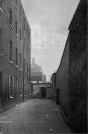An old, tall, brick wall on the right of a courtyard, and a four-story, dismal-looking, brick building on the left. A young boy is standing in one of the doorways of the building.