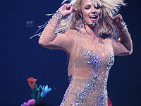 Britney Spears wearing a nude dress with crystals and is holding her arms at the height of her own head.