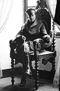 A man sits in an ornate chair. He is wearing a peaked cap, greatcoat and riding boots and holding a riding crop.