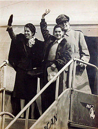 The MacArthur family standing at the top of the stairs leading from a passenger aircraft. Douglas MacArthur stands behind while his wife Jean and son Arthur wave to those below.