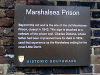 "Plaque headed ""Marshalsea Prison"", saying ""Beyond this old wall is the site of the old Marshalsea Prison, closed in 1842. This sign is attached to a remnant of the prison wall. Charles Dickens, whose father had been imprisoned here for debt in 1824, used that experience as the Marshalsea setting for his novel Little Dorrit."" ""HISTORIC SOUTHWARK"" is at bottom."