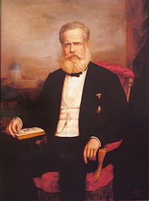 Painted portrait of bearded man in formal dress seated in an armchair with his left hand turning a page of an open book
