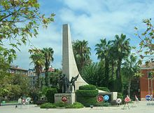 A tall sweeping stone triangle projects skyward behind the statues of a man and two children in bronze on a smaller podium. Around the base are place several wreathes with logos. Palm trees surround the scene.