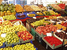 Dozens of baskets of brightly colored fruits and vegetables stacked around intersecting aisles at a market.