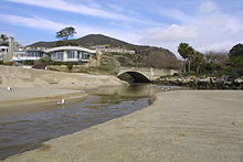 A creek flows out of a gap through a coastal mountain range and flows onto the beach.