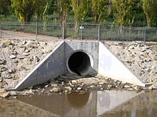 A large concrete hole opens out on a steep slope above muddy water