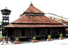 The wooden Kampung Laut mosque with its minaret and an onion-shaped dome on its tiled roof.