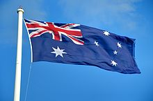A large Australian flag flying against the blue sky.