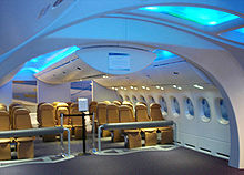 787 mock-up. It demonstrates the 787's spacious cabin. Above the brown seats are overhead bins.