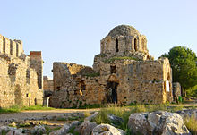 Ruins of a small stone domed structure built in a Byzantine style with tall windows. Grasses grow on the second level, as do trees behind it.