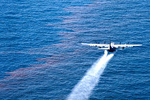 A large four propeller airplane spraying liquid over oil-sheen water
