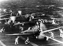 Planes on the deck of an aircraft carrier, with technical crews in white overalls attending the planes.
