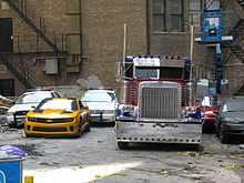 A Peterbilt 379, and a yellow Camaro are beside each other, with two police cars behind. They are near a building complex.