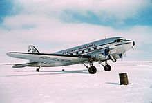 Right side view of an aircraft parked on snow-covered ground.