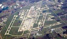 An aerial view of an airport, with long stretches of runway scattered across a large green patch.