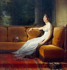 Woman with brown hair, in a white dress and tiara, sitting on a plush orange sofa