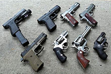 A collection of eight different handguns resting on the ground