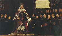 King Henry VIII in full royal regalia surrounded by a kneeling group of men who are all wearing black clothing and some with matching close-fitting caps