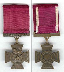 The obverse and reverse of the bronze cross pattée medal; obverse showing the crown of Saint Edward surmounted by a lion with the inscription FOR VALOUR with a crimson ribbon; the reverse shows the inscription of the recipient on the bar connecting the ribbon with the regiment in the centre of the medal.