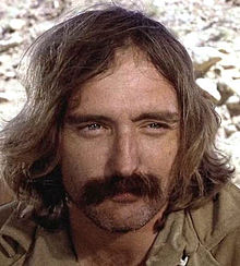 Dennis Hopper with shoulder-length brown hair and a handlebar mustache