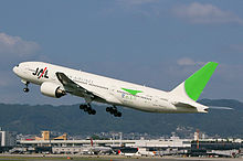A Boeing 777-200 aircraft in mid air during take-off, with the view of Itami Airport in the background