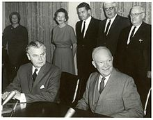 Diefenbaker and a smiling bald man in a suit sit at a table.  Two women and two men stand behind them.