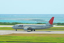 A Boeing 737-400 aircraft painted in Japan Transocean Air livery, travelling along the runway during take-off, with a clear green grass strip in the foreground and a blue sea view in the background