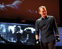 A man wearing a gray shirt, brow pants and black gloves stands in front of a screen, where scenes from Minority Report are being projected.