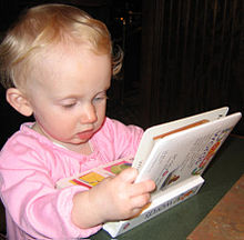 A baby leans at a table staring at a picture book with intense concentration.