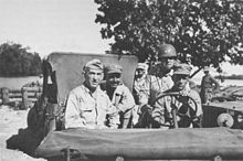 Four officers in a jeep, with a steel helmeted driver. The one on the left is wearing a garrison cap with three stars, the one in the centre a cloth peaked cap with one star, while the one on the right had a steel helmet with two stars.
