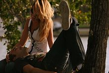 A young couple relax under a tree. The man lies on his back looking up at the woman. The woman, with striking long blond hair and sunglasses, is seated by his head, looking down at him and with her hand placed round his head. Both are laughing