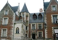 Photo of a large medieval house, built of brick with many windows and gables and a circular tower with a conical roof.