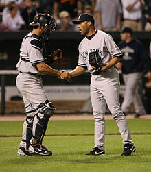 Jorge Posada wearing catcher's equipment shakes hands with Mariano Rivera on a grass field.