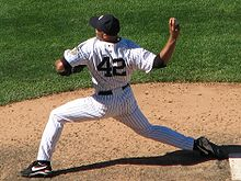 "Mariano Rivera in a white pinstriped baseball uniform and navy blue cap stands on a dirt mound. He is striding forward to the left as he clutches a baseball behind his head. The back of his uniform reads ""42"" in navy blue numbers."