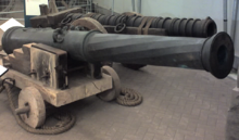 Two large metal cannons of differing designs, one in front of the other