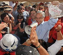 Color image of President Piñera displaying the message in a plastic document protector sent by the miners with Mining Minister Golborne