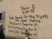 "A woman, at the left of the image, is reading a black spray paint message written on a brick wall. The message reads ""Team 5 4-19-95 We Search For the truth We Seek Justice. The Courts Require it. The Victims Cry for it. And God Demands it!"""