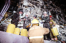 Several Air Force members and firefighters are clearing debris from the damaged building. Several yellow buckets are visible, which are being used to hold the debris. The destruction of the bombing is visible behind the rescuers.