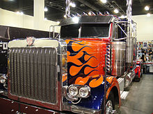 A Peterbilt 379 truck is seen at BotCon 2011, it is beside a promotional poster of the film, with people behind the truck.