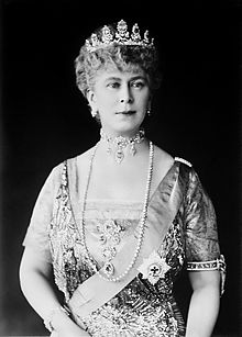 Lady in tiara and gown wearing a choker necklace and a string of pearls