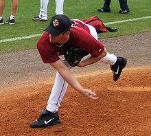 right-handed pitcher wearing a red Astros uniform throws a baseball from a pitching mound.