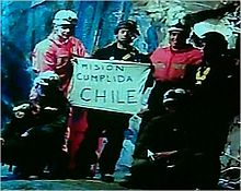 "Slightly grainy color video capture image of the six rescuers displaying the famous ""Mision Cumplida Chile"" sign deep within San José Mine near Copiapo, Chile [125]"