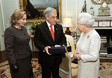 Color image of Chilean President Piñera and the First Lady present a souvenir gift rock from the San Jose Mine to Queen Elizabeth II on 18 October 2010 during a state visit to the UK