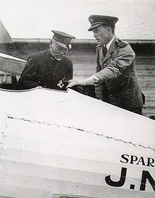 Two men standing over the interior of an airplane's cockpit.