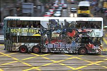 A bus with Optimus Prime and Chinese characters printed on its side drives across a street.